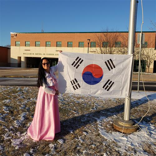 Mrs. San Bento in front of Davies with the flag of South Korea